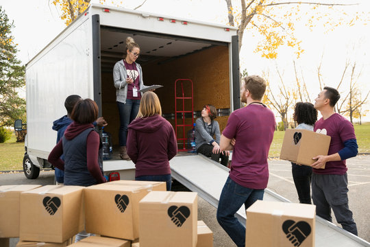 Woman with clipboard leading volunteers with cardboard boxes at truck