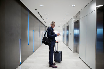 Businessman with luggage texting waiting for elevator in airport corridor