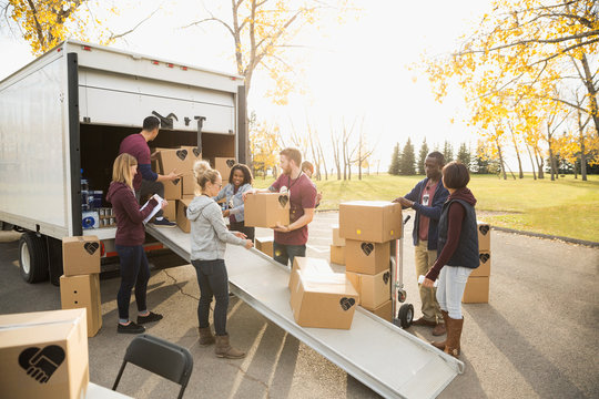 Volunteers unloading cardboard boxes from truck in sunny autumn parking lot