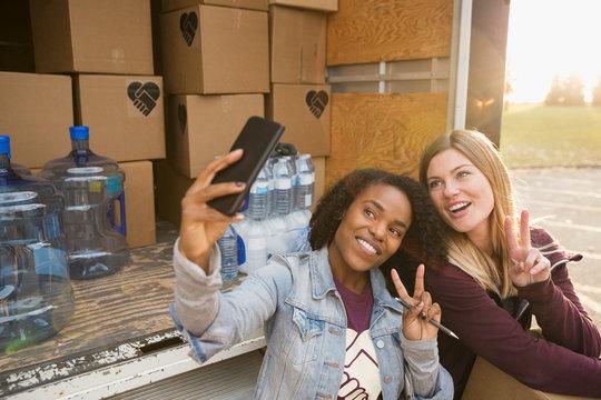 Smiling female volunteers taking selfie gesturing peace sign with camera phone at truck