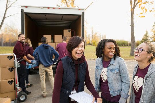 Female volunteers laughing outside truck