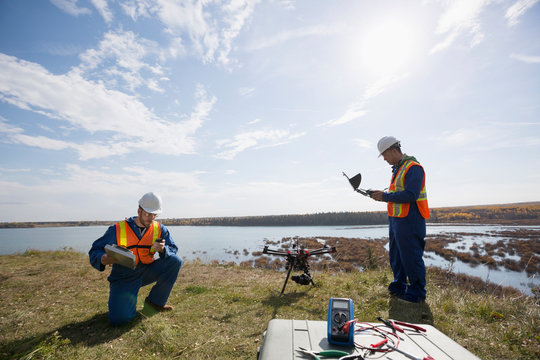 Surveyors with drone equipment on sunny hilltop overlooking lake