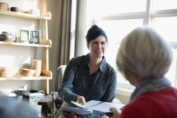 Financial advisor giving portfolio to senior woman meeting in living room