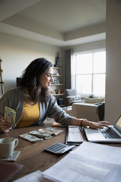 Young woman counting cash at laptop in dining room