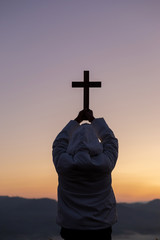 Silhouette human praying and holding christian cross for worshipping God at sunset...