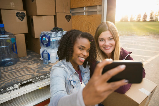 Smiling female volunteers taking selfie with camera phone at truck