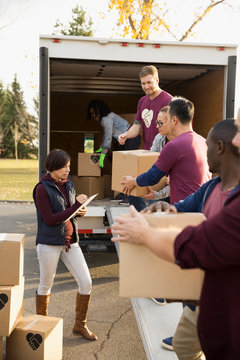 Woman with clipboard leading volunteers loading cardboard boxes onto truck
