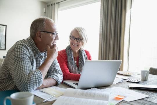 Smiling senior couple with laptop talking paying bills online in dining room