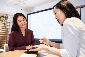 女性社員たちがタブレットを見ながら打ち合わせをしている