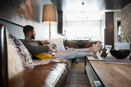 Man with laptop playing guitar on living room sofa
