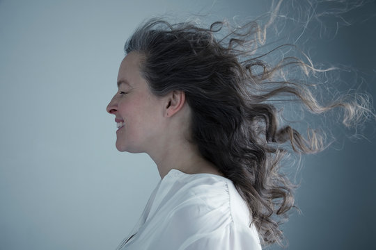 Profile portrait wind blowing long curly hair of Caucasian mature woman with eyes closed