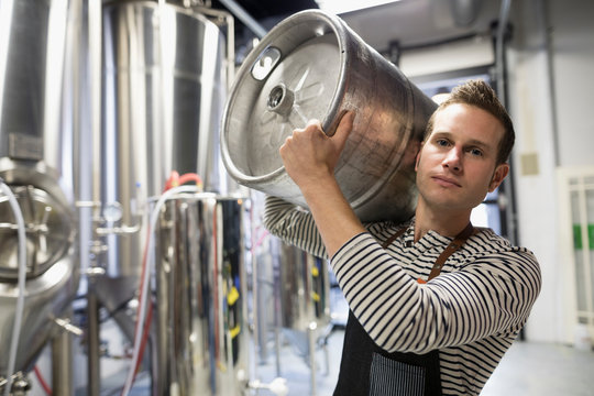 Portrait confident male brewer carrying keg in brewery