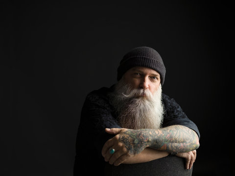 Portrait confident tattooed hipster man with long gray beard against black background