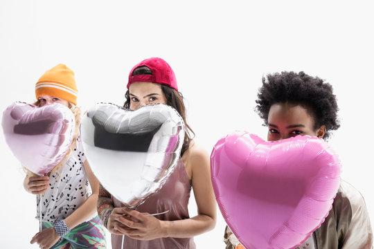 Portrait smiling women friends hiding behind heart-shape balloons against white background