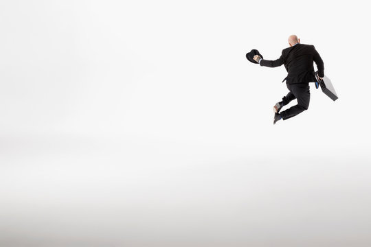 Playful businessman with briefcase jumping, clicking heels against white background