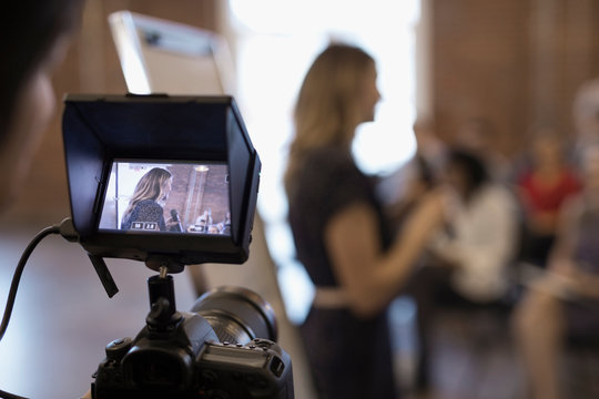 Digital viewfinder videoing of businesswoman leading conference meeting