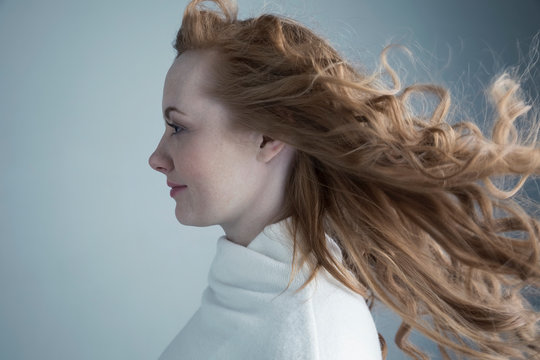 Profile portrait wind blowing through long, curly red hair of Caucasian woman
