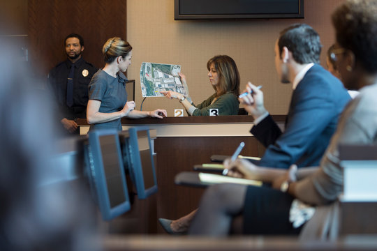 Female attorney and expert witness with satellite image in legal trial courtroom