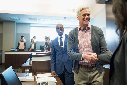 Smiling defendant and attorney handshaking in legal trial courtroom