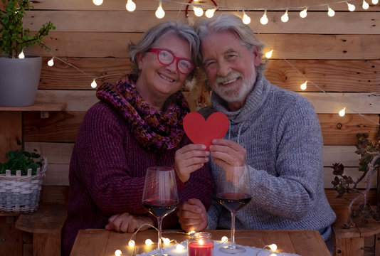 A romantic Valentine's Day for an elderly couple sitting outdoors on a rustic wooden bench holding a red heart in their hands. Two older people celebrate love with wine glasses and sparkling lights