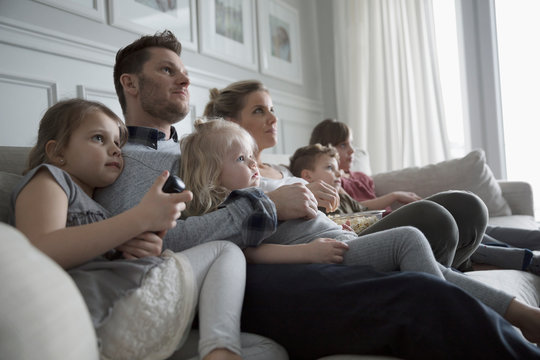 Young family watching TV on living room sofa