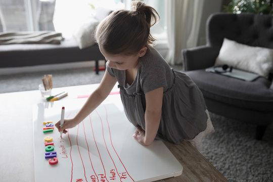Girl making chore list on whiteboard