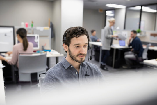 Businessman talking on telephone with headset at cubicle