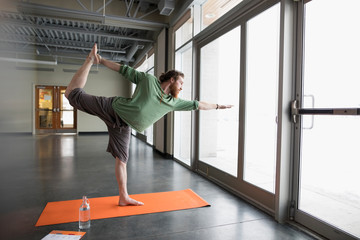 Man practicing yoga king dancer pose on yoga mat in gym studio