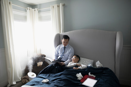 Businessman father reading book to sick son laying in bed