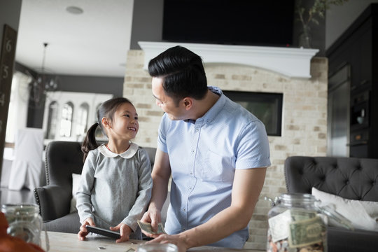 Father teaching daughter counting allowance money