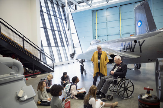 Docent and war veteran talking to students on field trip at Naval airplane in war museum hangar