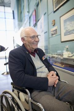 Portrait smiling senior male war veteran in wheelchair in war museum