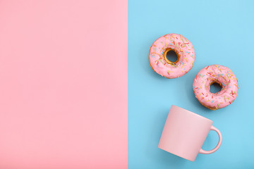 Sweet donuts pink and blue with a mug of coffee. Blue and pink background, game of colors, color conflict. Mock up for design. Copy space.