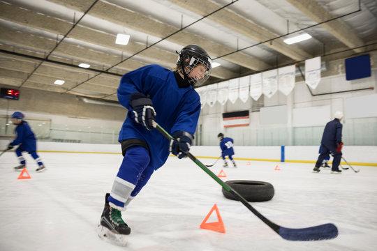 Boy ice hockey player practicing drills on ice hockey rink