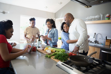 Affectionate African American family cooking in kitchen
