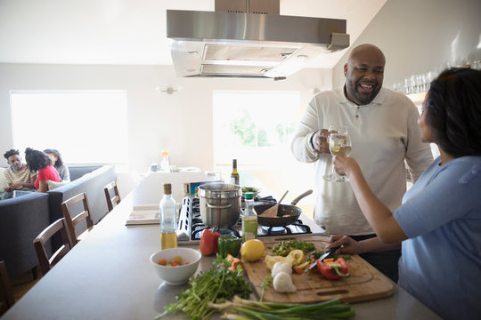 African American couple cooking and drinking white wine in kitchen