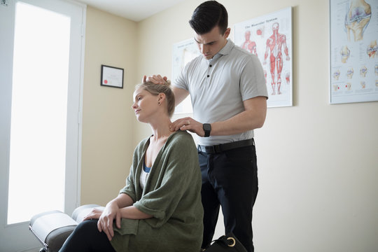 Male physiotherapist examining neck of woman in clinic examination room