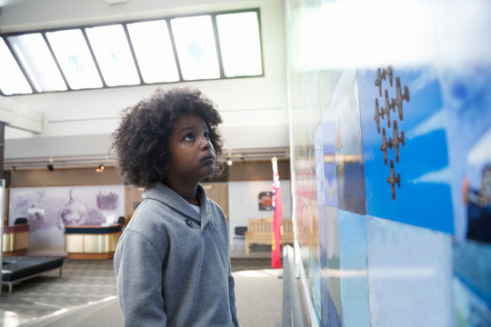 Curious African American boy student looking up at exhibit photographs in war museum