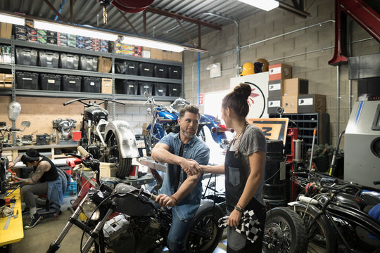 Male customer on motorcycle shaking hands with female mechanic in auto repair shop