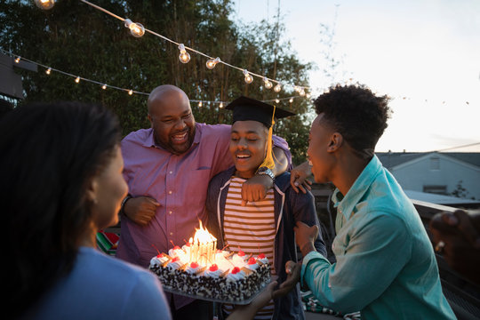 African American family celebrating graduation with cake on summer deck