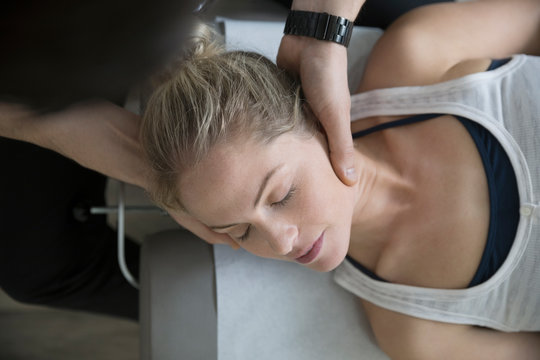 Chiropractor adjusting neck of woman on clinic examination table