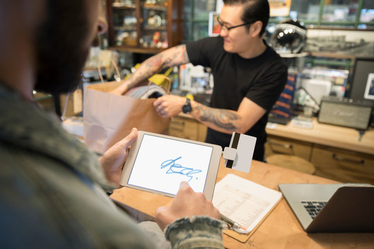 Customer using touch signature on digital tablet at counter in motorcycle shop