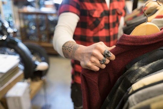 Male customer with tattoo and rings shopping, browsing at clothing in shop