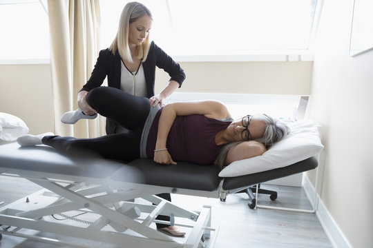 Female physiotherapist stretching leg of client in clinic examination room