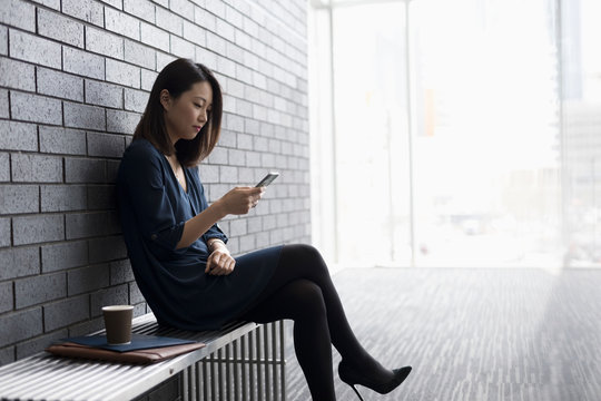 Businesswoman texting with cell phone on bench in office