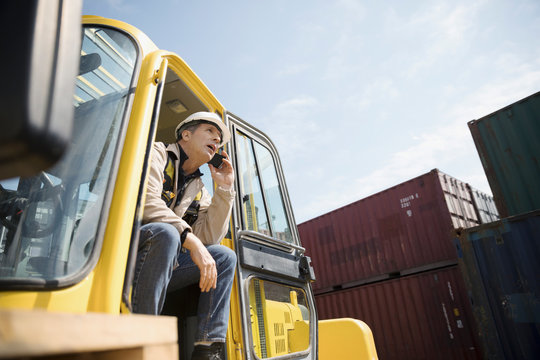 Male forklift driver talking on cell phone in sunny industrial container yard