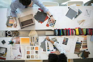 Overhead view designers with fabric swatches in conference room meeting
