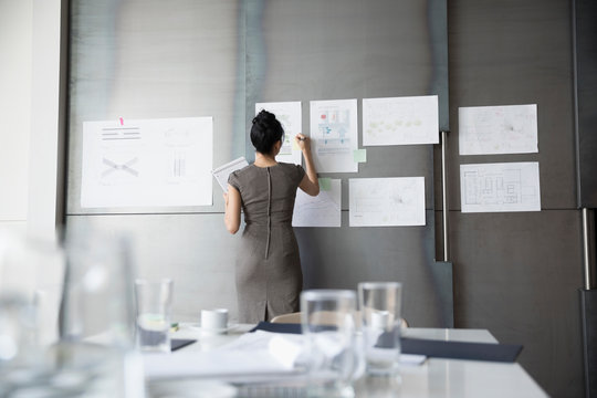Businesswoman brainstorming, reviewing analytics in conference room