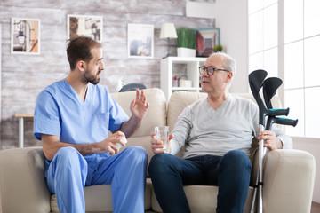 Bearded doctor in nursing home giving pills