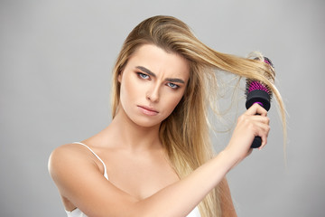 angry woman brushing her long blond hair and looking to camera with anger